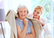 caregiver putting a blanket into an elder woman