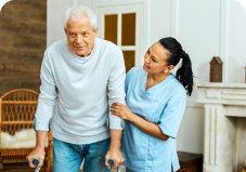 caregiver assisting an elder man to walk
