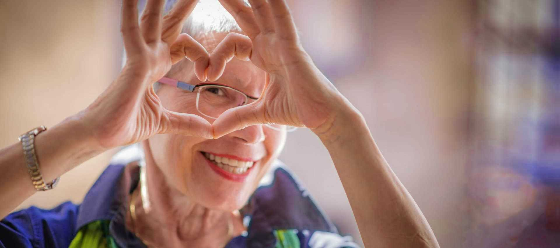 elder woman forming a heart between her fingers